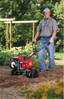 Gas powered tiller used in garden.