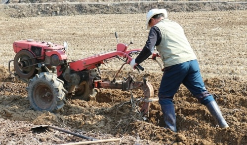 Man using rototiller.