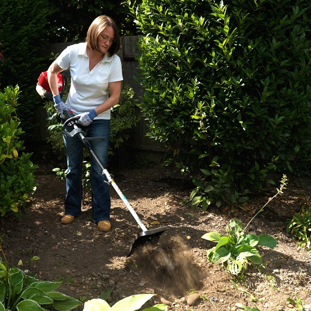 Woman Using Cultivator Attachment For Garden Beds
